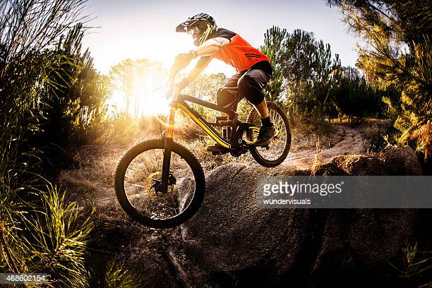 Extreme mountain biker riding over rough terrain