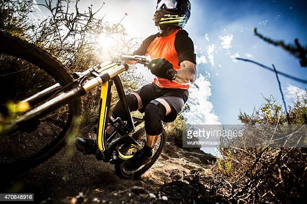 Extreme mountain biker speeding down a dirt road