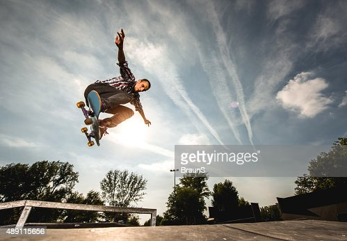 Extreme skateboarder in Ollie position against the sky.