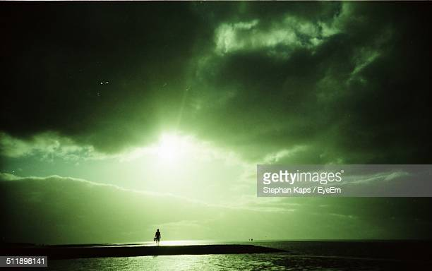 Extreme sky at sea with silhouette of a man