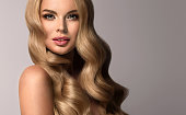 Young, blonde haired woman  with voluminous, shiny and wavy hair. Beautiful model with long, dense and curly hairstyle, vivid make-up and  pale rose lipstick on the lips.