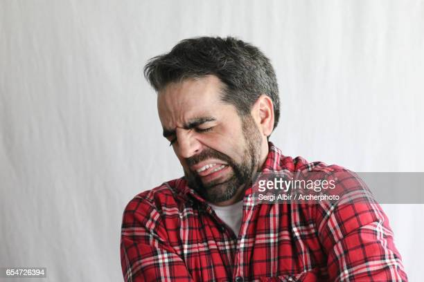 Extremely expressive guy in his late 30s: disgusted or aching