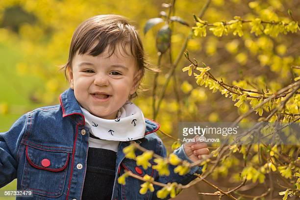 Extremely happy toddler boy close to tree