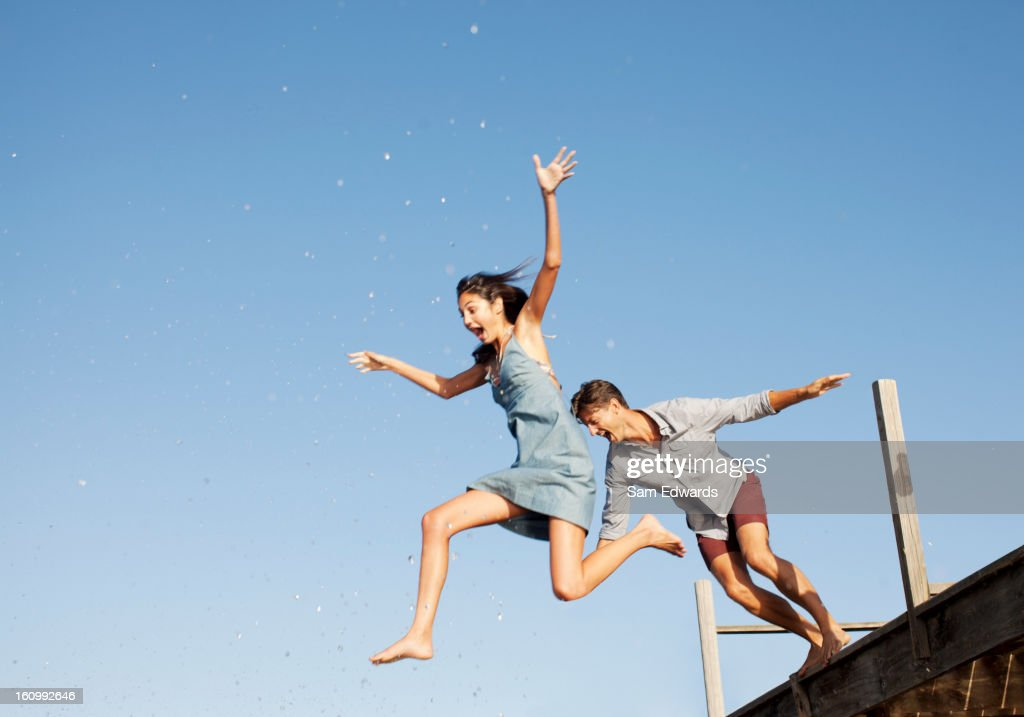 Exuberant couple jumping off dock : Stock Photo