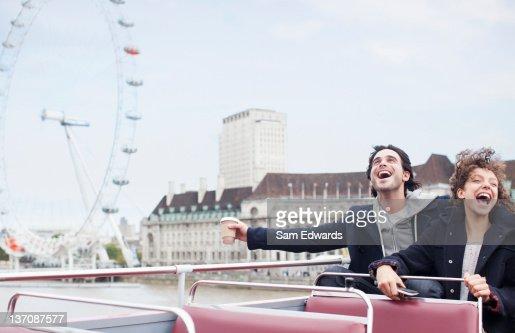 Exuberant couple riding double decker bus in London : Stock Photo