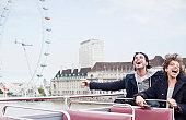Exuberant couple riding double decker bus in London