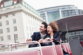 Exuberant couple riding double decker bus in London
