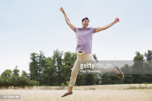 Exuberant man jumping in rural field : Stock Photo