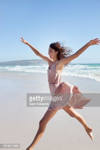 Exuberant woman running on beach with arms outstretched