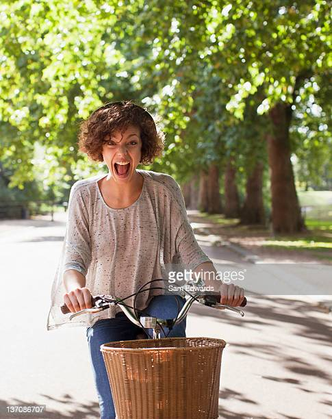 Exuberant woman with mouth open riding bicycle in park
