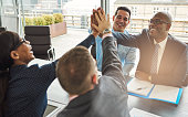 Exultant team of multiracial young business professionals rejoicing and congratulating each other giving a high fives gesture