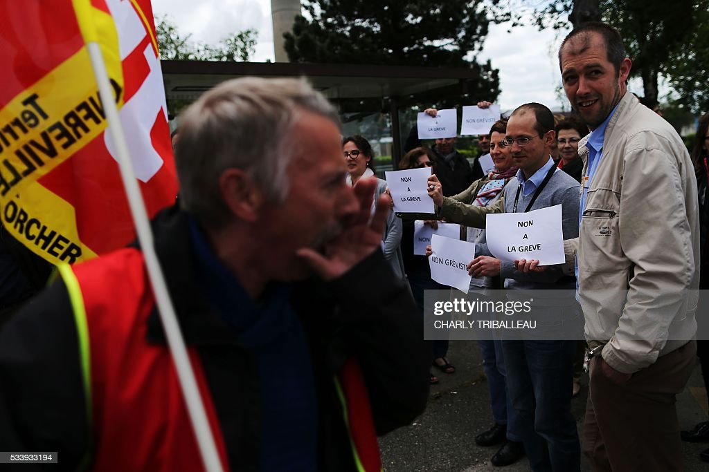 Exxon employees hold signs reading 'Non striker' and 'No to the strike' (R) as they stand in front of a French CGT union member at the ExxonMobil oil refinery in Notre-Dame-de-Gravenchon, northwestern France, on May 24, 2016, during blockades and strikes at several oil refineries and fuel depots in France by protesters opposed to government labour reforms. A strike called by the Force Ouvriere (FO) and General Confederation of Labour (CGT) French workers' unions started slowing on May 24 at the ExxonMobil oil refinery in Notre-Dame-de-Gravenchon, without disrupting operations at France's second largest refinery. Six out of eight of the refineries in France have either stopped operating or have reduced output due to strikes and blockades. / AFP / CHARLY
