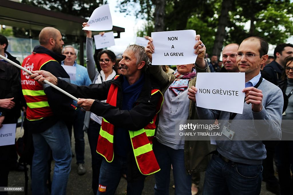 Exxon employees hold signs reading 'Non striker' as they stand near French CGT union members at the ExxonMobil oil refinery in Notre-Dame-de-Gravenchon, northwestern France, on May 24, 2016, during blockades and strikes at several oil refineries and fuel depots in France by protesters opposed to government labour reforms. A strike called by the Force Ouvriere (FO) and General Confederation of Labour (CGT) French workers' unions started slowing on May 24 at the ExxonMobil oil refinery in Notre-Dame-de-Gravenchon, without disrupting operations at France's second largest refinery. Six out of eight of the refineries in France have either stopped operating or have reduced output due to strikes and blockades. / AFP / CHARLY