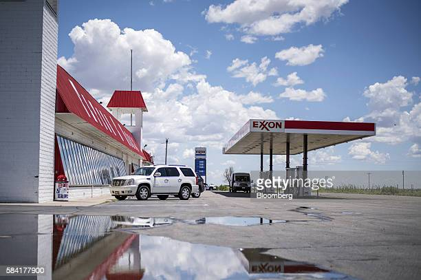 Exxon signage is reflected in a puddle as customers put fuel in their vehicles at a roadside Exxon gas station outside Aurora New Mexico US on...
