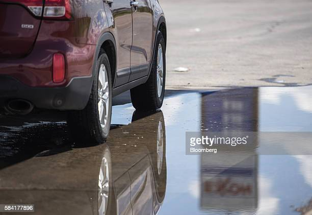 Exxon signage is reflected in a puddle at a roadside Exxon gas station outside Aurora New Mexico US on Tuesday July 26 2016 Exxon Mobil Corp is...