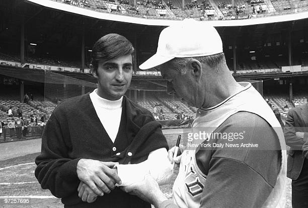 ExYankee great Joe DiMaggio now Oakland A's VP and coach signs cast of sidelined Joe Pepitone prior to game at Yankee Stadium