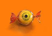 Eye ball halloween candy on orange background, 3d