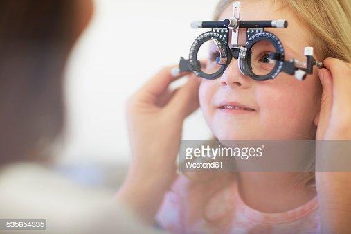 Eye doctor examining girls vision