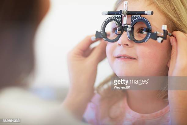 Eye doctor examining girls vision