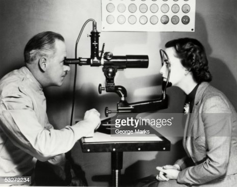 Eye doctor examining patient : Stock Photo