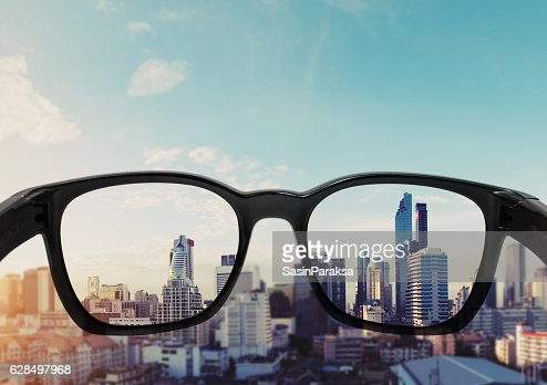 Eye glasses looking to city view, focused on glasses lens : Stock Photo