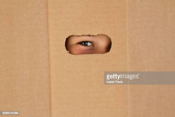 Eye looking through a hole on cardboard