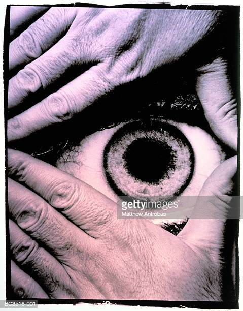 Eye looking through aperture created by two hands (toned B&W)
