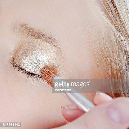 Eye makeup artist applying eyeshadow : Stock Photo