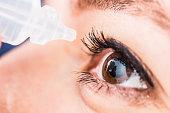 Bucharest, Romania - June 18,2016 : Closeup of eyedropper preparing to release fluid drops in the brown eye