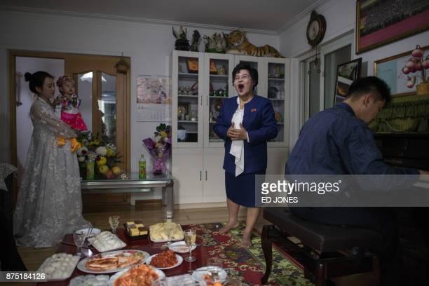 TOPSHOT Eyeglass shop manager Song SongHui sings for her family members in her apartment in Pyongyang on November 17 2017 / AFP PHOTO / Ed JONES
