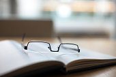 Eyeglasses and book on conference table