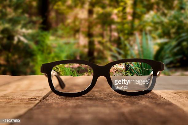 Eyeglasses on rustic wooden table. Forest background.