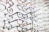 Large group of eyeglasses in an eyewear store display.