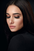 Eyelashes Makeup. Woman Beauty Face With Long Black Lashes Extensions And Beautiful Makeup On Black. High Resolution