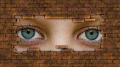 Womans eye peeking through a hole in wall