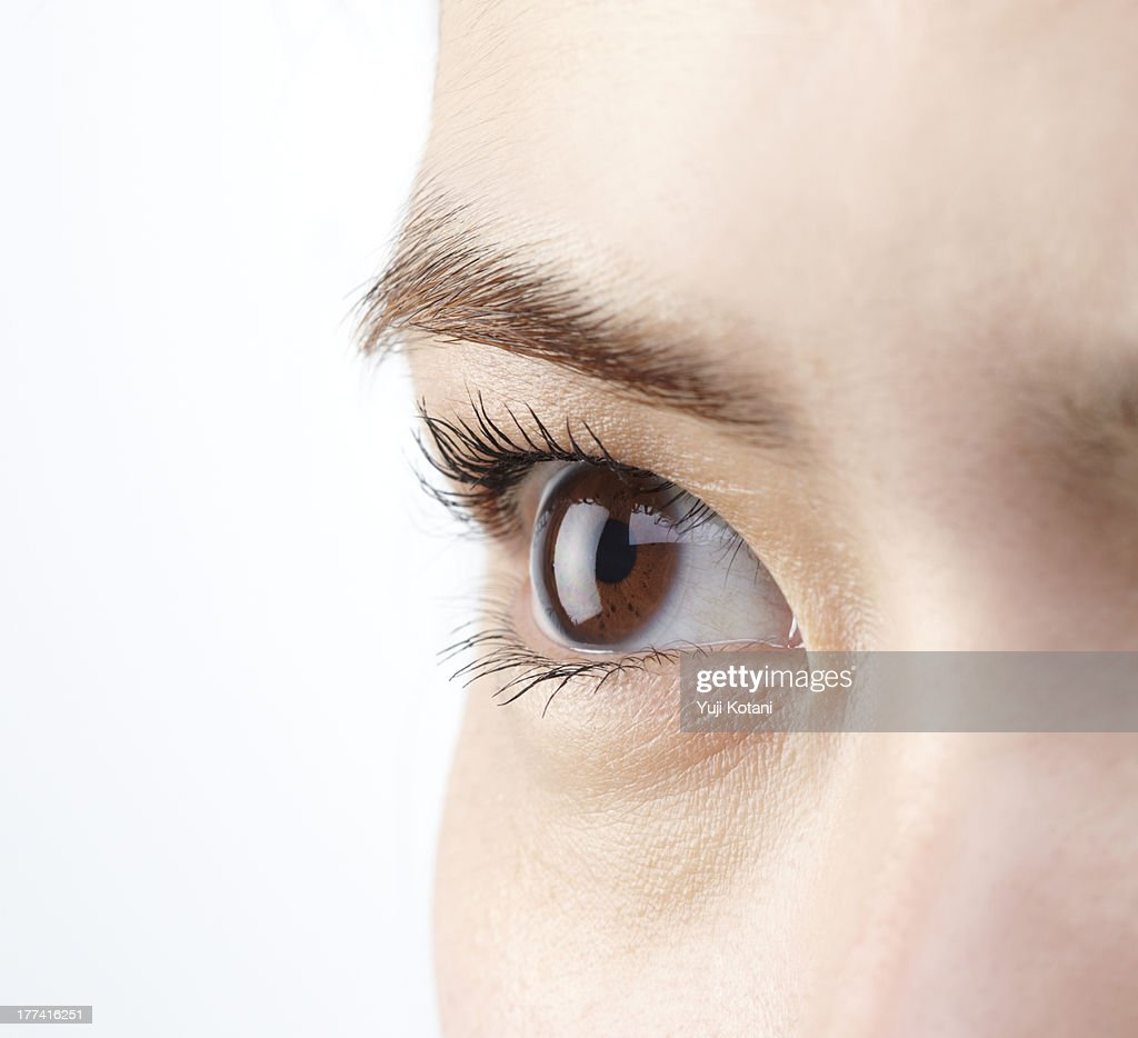 Eyes of a woman attaching a contact lens : Stock Photo
