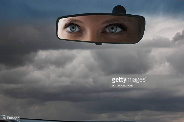 Eyes of Caucasian woman reflecting in rear view mirror