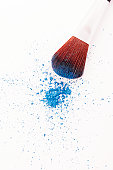 Eyeshadow brush and loose blue eyeshadow powder, close-up