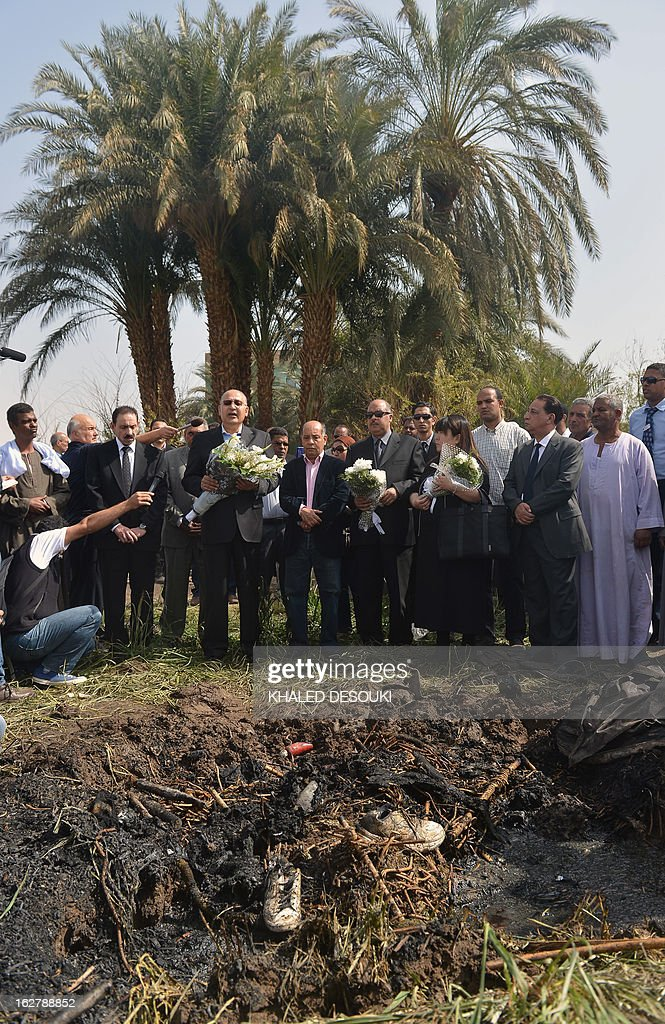 Ezat Saad, Governor of the ancient temple city of Luxor (C-L) and Japanese Okumura Hatsuko (C-R) director of Japanese division in an Egyptian travel agency lay flowers at the site of a hot air balloon accident on February 27, 2013. An initial probe into a hot air balloon crash that killed up to 19 tourists in Egypt has ruled out any criminal activity as a cause of the accident, state media said.