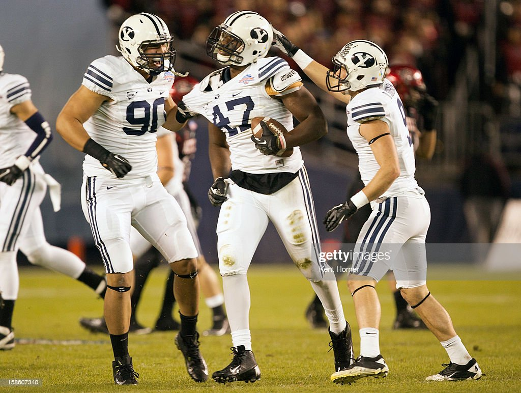 Ezekial Ansah #47 of the BYU Cougars celebrates with teammates Branson Kaufusi #90 and Daniel Sorensen #9 after intercepting the ball in the first half of the game against the San Diego State Aztecs in the Poinsettia Bowl at Qualcomm Stadium on December 20, 2012 in San Diego, California.