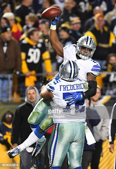 Ezekiel Elliott is hugged by Travis Frederick of the Dallas Cowboys after rushing for a 32 yard touchdown in the fourth quarter during the game...