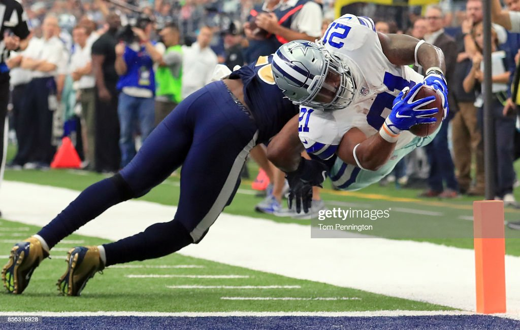 Ezekiel Elliott #21 of the Dallas Cowboys dives into the end zone to score a touchdown against Mark Barron #26 of the Los Angeles Rams in the second quarter at AT&T Stadium on October 1, 2017 in Arlington, Texas.