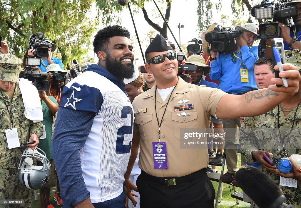 Ezekiel Elliott #21 of the Dallas Cowboys takes photos with members of the military after a day of training camp on July 24, 2017 in Oxnard, California.