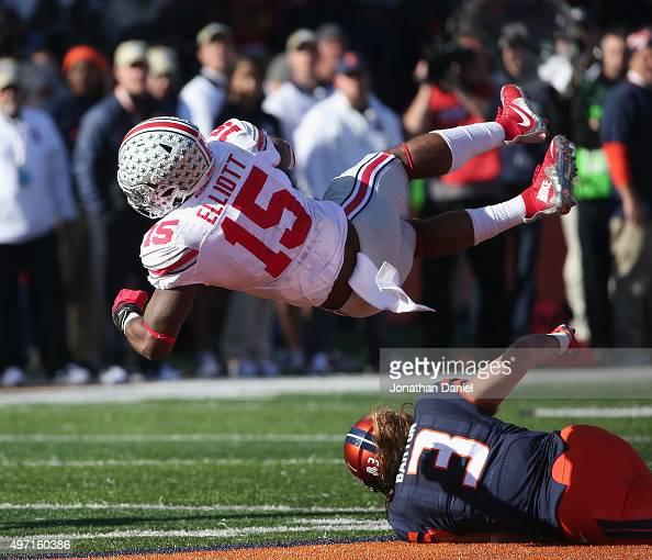 Ezekiel Elliott of the Ohio State Buckeyes is tripped up by Taylor Barton of the Illinois Fighting Illini at Memorial Stadium on November 14 2015 in...