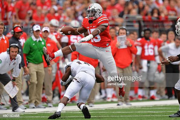 Ezekiel Elliott of the Ohio State Buckeyes leaps over Darius Phillips of the Western Michigan Broncos for a first down gain in the second quarter at...