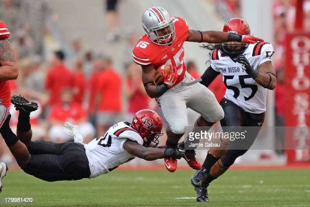 Ezekiel Elliott of the Ohio State Buckeyes leaps to attempt to avoid the tackle of Nat Berhe of the San Diego State Aztecs in the third quarter after...
