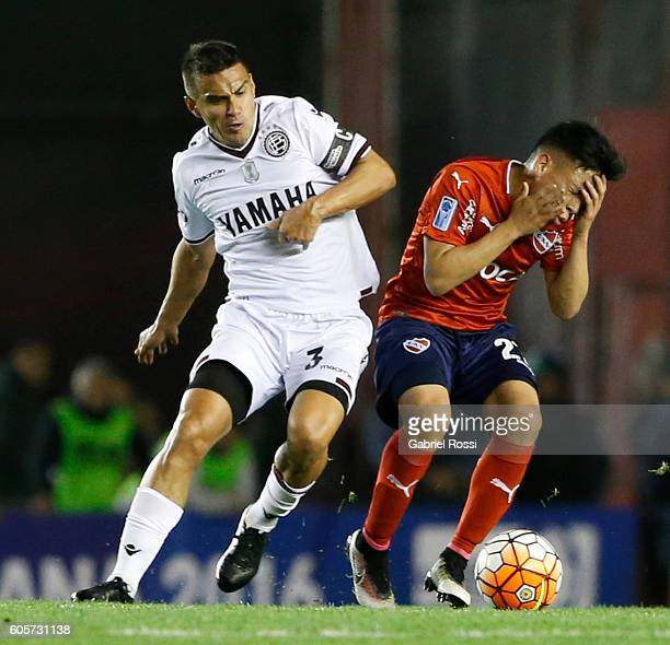 Ezequiel Barco of Independiente is fouled by Maximiliano Velazquez of Lanus during a match between Independiente and Lanus as part of Copa...