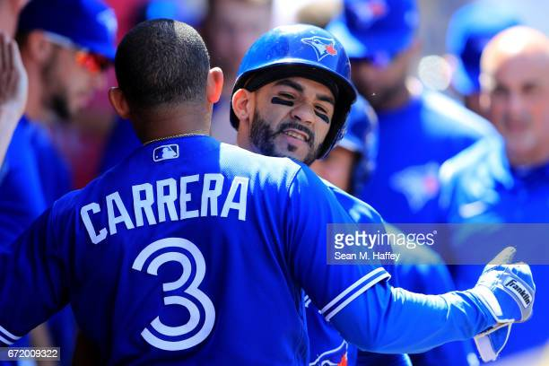 Ezequiel Carrera congratulates Devon Travis of the Toronto Blue Jays after he hit a tworun homerun during the eighth inning of a game against the Los...