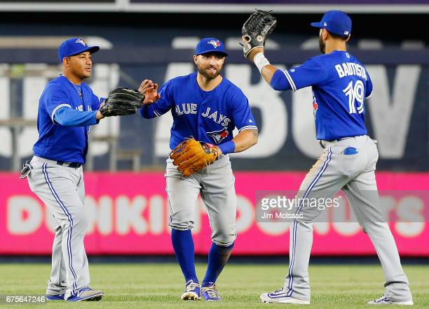 Ezequiel Carrera Kevin Pillar and Jose Bautista of the Toronto Blue Jays celebrate after defeating the New York Yankees at Yankee Stadium on May 1...