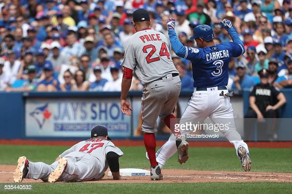 Ezequiel Carrera of the Toronto Blue Jays beats out an infield single in the seventh inning during MLB game action as Travis Shaw of the Boston Red...